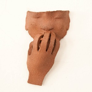 """Hot"" by Judith Eloise Harper. In this demonstration of the American Sign Language symbol for the word 'hot,' the figure appears to be soothing his singed fingertips with a cooling breath. Measuring 7"" long, 4"" wide and 2"" deep, ""Hot"" is made of grog-infused terra cotta-look clay."